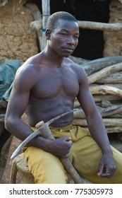 GUILI, CAMEROON - 7TH JULY 2012: A strong muscular man from Cameroon, is sitting and thinking. He is holding a pickaxe in his right hand.
