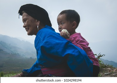 Guilin, China - 15th June 2015 : A shot of a grand mother carrying his grand children on her back for a morning walk at a paddy terrace in Guilin China.