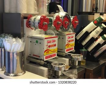 GUILIN, CHINA - CIRCA NOVEMBER 2018 : Electric semi automatic bubble tea cup SEALING MACHINE at cafe.