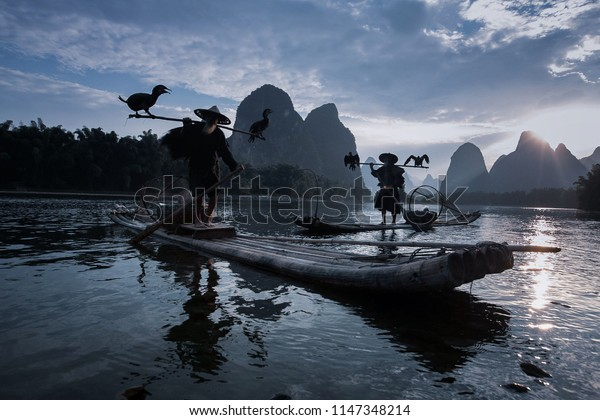 GUILIN, CHINA, JUNE 17, 2018;The 80-year-old uncle Guilin body out fishing with a bamboo raft and black crow