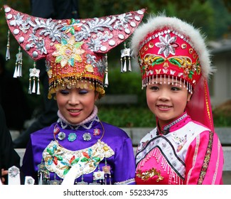 GUILIN, CHINA - NOV 4, 2007: Two young chinese woman in stylized ethnic dresses. Guangxi province is home to 11 minority groups