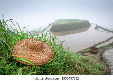 Guilin, China rice terraces and workers hat with heavy fog.