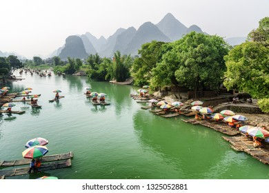 Guilin, China - September 19, 2017: Tourist bamboo rafts on the Yulong River in Yangshuo County. Scenic karst mountains are visible in background. Yangshuo is a popular tourist destination of Asia.