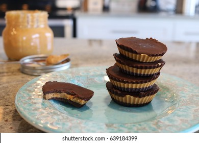Guilt free homemade organic dark chocolate peanut butter cups.  Stacked on a fancy blue plate with homemade peanut butter in a jar with a spoon will a yummy scoop of peanut butter in the background