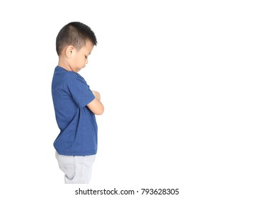 Guilty and abused little asian boy standing with arms crossed