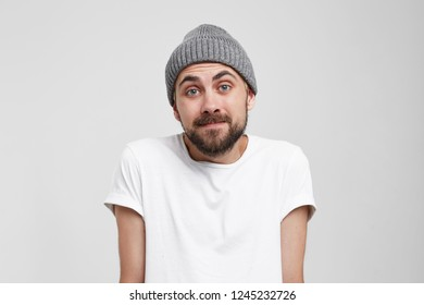 Guilty and confused young man shrugging shoulders, making helpless gesture with hands, having Oops expression on his face. Feeling sorry for doing something wrong,over white background