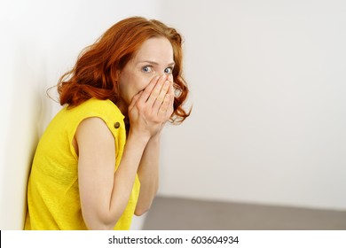 Guilty or embarrassed young redhead woman covering her lower face with her hands and glancing sideways at the camera with big eyes as she leans against a wall