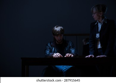Guilty man and elderly policewoman in dark room