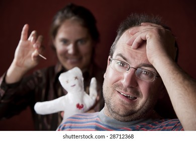 Guilty man with upset woman poking voodoo doll in the background