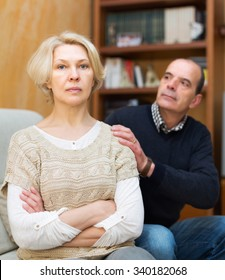 Guilty senior husband asking wife for forgiveness at home