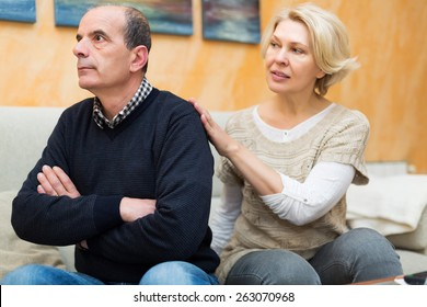 Guilty senior wife asking husband for forgiveness at home