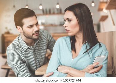 Guilty young man is asking forgiveness in girlfriend. Offended woman is looking at him with mistrust while holding smartphone