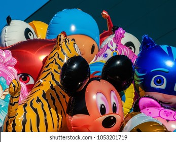 Guimaraes, Portugal - December 23, 2017: Balloons with the shape of cartoon characters on sale at a concert of a band for children, with Mickey Mouse, Catboy from PJ Masks and others
