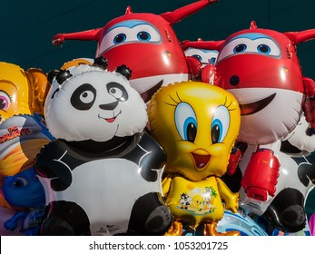 Guimaraes, Portugal - December 23, 2017: Balloons with the shape of cartoon characters on sale at concert of band for children with Tweety Bird, Jett of Super Wings, Smurfette of The Smurfs and others