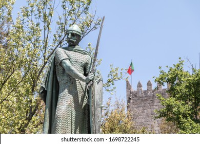 Guimaraes, Portugal - May 10, 2018: statue of the first king of Portugal, D. Afonso Henriques by the sculptor Antonio Soares dos Reis in front of the castle of Guimaraes that tourists are visiting
