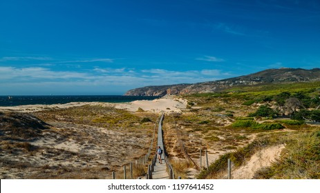 Guincho, Portugal - Oct 6, 2018: Tourists at steps that lead to the Atlantic Ocean found in Guincho beach near Lisbon, Portugal