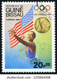 GUINEA BISSAU - CIRCA 1984: post stamp printed in Guine Bissau shows national flag, gold medal and Tracie Ruiz, synchronized swimming, US; 1984 Olympic winners; Scott 614 A82 20p, circa 1984