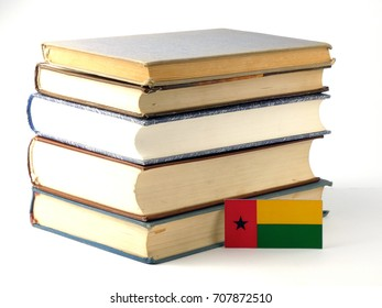 Guinea Bissau flag with pile of books isolated on white background