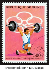 """GUINEA - CIRCA 1995: A stamp printed in Guinea from the """"Olympic Games, Atlanta 1996"""" issue shows weightlifting, circa 1995."""