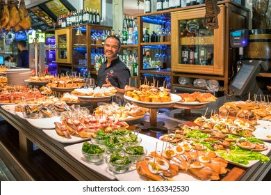 Guipuzcoa, Basque Country, Spain - august  02, 2018: Waiter and assortment of skewers inside a typical bar in the historic center of the city of San Sebastian