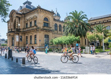 Guipuzcoa, Basque Country, Spain - august  02, 2018: Backlit scene of people walking and cycling in the garden area in the back of the town hall of the city of Donosti - San Sebastian