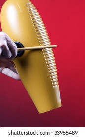 A guiro gourd percussion instrument being played against a red background in the vertical format with copy space.