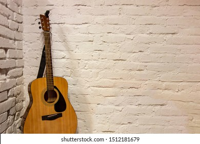Guitar against white background. Acoustic musical instruments stands leaning on brick wall with empty copy space to add text of image. Music backdrop