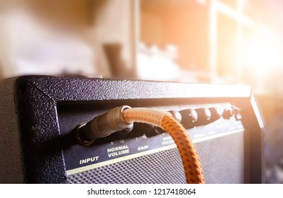 Guitar amplifier with audio cable in recording studio background beautiful sunlight and copy space, Music concept. Selective focus. Warm tone image