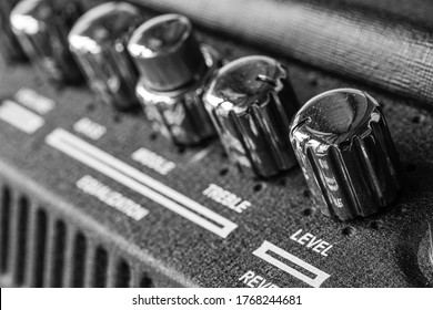 Guitar amplifier macro photography. Control knobs. Electric playing equipment. Black and white picture.