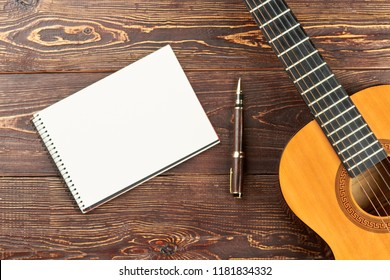 Guitar with blank notebook and pen. Workspace with blank notebook, pen and acoustic guitar on brown wooden table background. Work space of songwriter.