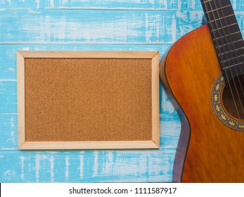 The guitar and board on blue wooden texture background. Music day concept.