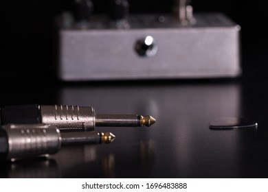 Guitar cable and guitar pick. Close-up of jacks. Guitar effect stompbox in the background