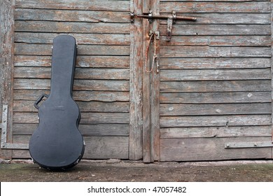 The guitar case rest on a gate.