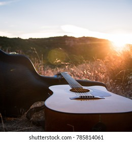 Guitar & Case sitting in a meadow on top of a mountain in the morning sun.