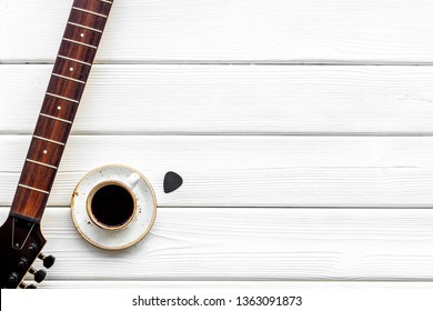 guitar and coffee for song writer on white wooden background top view space for text