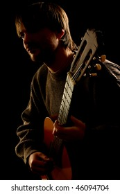 Guitar concert. Silhouette of guitar player in darkness. Guitarist isolated on black background.