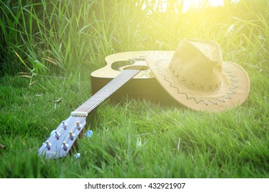 Guitar and cowboy hat on a grass