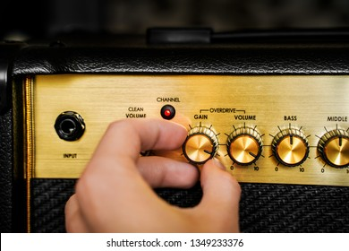 Guitar electric amplifier. Hand turning volume control knob up to the max. Rock music overdrive effect