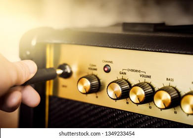 Guitar electric amplifier. Rock overdrive effect. Hand is plugging a cable into jack. Max volume knob. Shallow depth of field