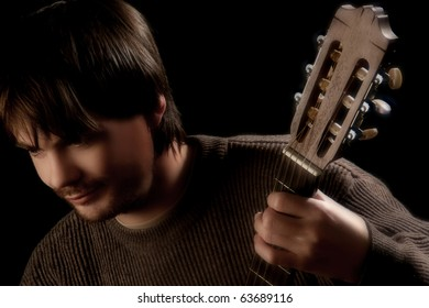 Guitar fingerboard and guitarist. Artistic portrait of man with hand on fingerboard. Black background