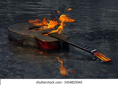 Guitar In Flames And Black Smoke Reflection In Water. Burning Guitar In River Water. Burning Musical Instrument On Dark Surface Of  Water. Concept Of Crisis Of Authorship.