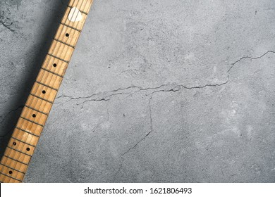 Guitar fretboard (neck) on a cracked concrete background. Space for copy