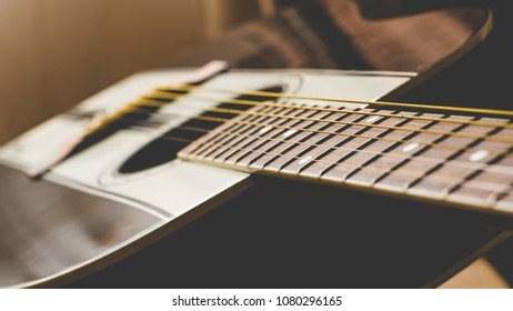 Guitar fret-board with a shallow focus.  Overall image has an aged look.