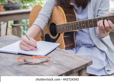 Guitar with girl's hand composing music on the wooden table