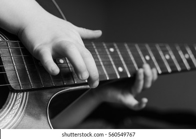Guitar in the hands of a child of a little girl playing music. Black and white