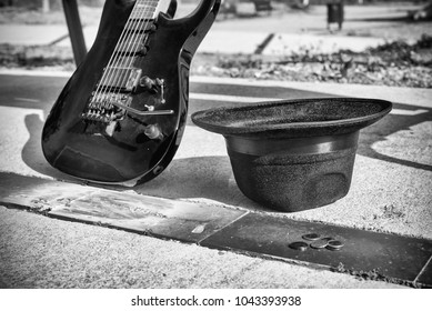 Guitar and hat next to a park bench, an artist poverty concept