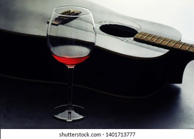 Guitar and high glass with red wine on a stone background. Desk musician, headphones, microphone and more.
