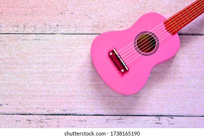 guitar home lesson , pink wooden retro guitar for girl laying on pink wooden floor