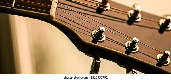 Guitar instrument, frets, strings & tuning pegs, close up in real country n western / folk, authentic style.