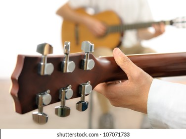 Guitar lesson or two musicians playing together, shot from behind one guitar, with shallow focus